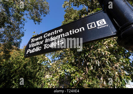 Signpost in Kelso, Scotland, pointing visitors to the centre with information and toilets. - Stock Image