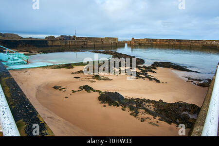 Tidal pool in Portknockie harbour, an old Scottish fishing village located in Moray Firth, UK. - Stock Image