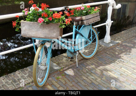 Old-fashioned city bike near a bridge over canal in the Old Town of Delft, Holland - Stock Image
