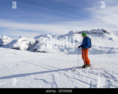 Male skier skiing in Le Grand Massif ski area looking at snowcapped mountains in the French Alps. Flaine, Rhone-Alpes, France - Stock Image