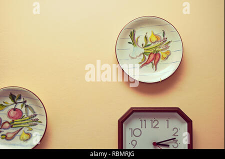 kitchen wall with decorative plates and clock - Stock Image