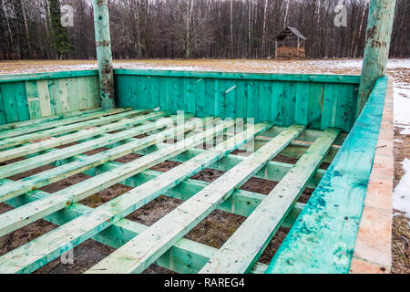 European bison and forest game new empty feeding rack in Bialowieza, Poland, partly snow, green hayrack, cloudy winter day, old rack in the background - Stock Image