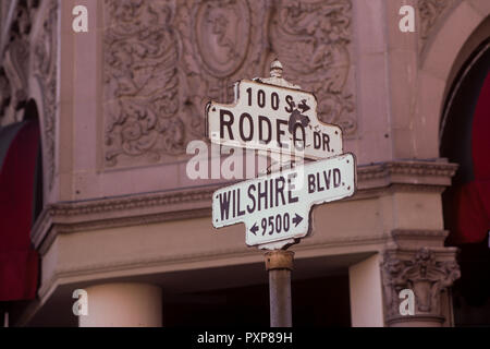 Street sign of the crossing of Rodeo Drive and Wilshire Boulevard in Beverly Hills, Los Angeles, California, USA. Picture also shows part of the Beverly Hilton hotel in the background. - Stock Image