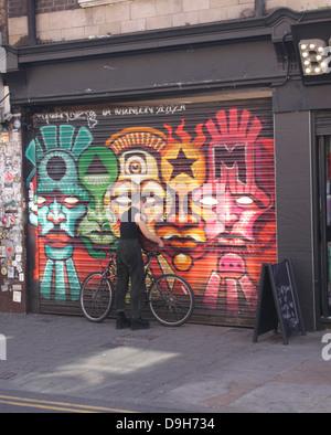 Graffiti and cyclist at Brick Lane London June 2013 - Stock Image