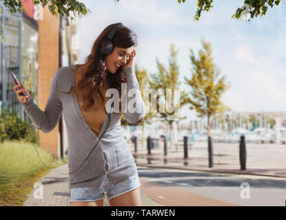Woman standing outdoors listening to music using headphones - Stock Image