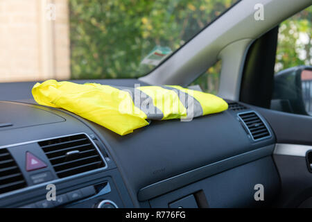 Yellow vest on a dashboard car in protest against tax increases in France - Stock Image