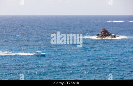 Power boat off Grand Fond with a small rock island, St Barts - Stock Image