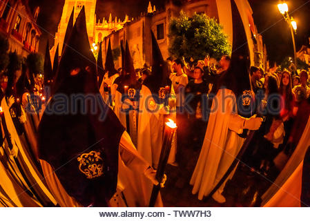 Hooded Penitents (Nazarenos) in the procession of the Brotherhood (Hermandad) San Benito, Holy Week (Semana Santa), Seville, Andalusia, Spain. - Stock Image