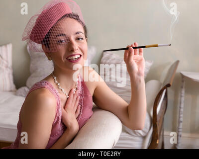 Sensual 1920s woman in pink flapper dress sitting on an antique chaisee longue or recliner - Stock Image