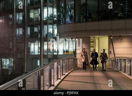 Business people walking on urban pedestrian bridge at night - Stock Image