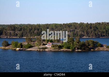 Swedish idyllic summer landscape with island in Stockholm archipleago and swedish national flag - Stock Image