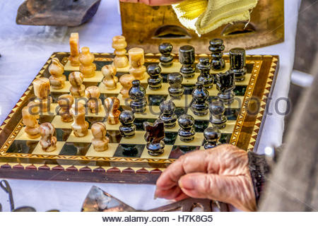 Old wood and ivory handmade chessboard with wood pieces on sale on a flea market - Stock Image
