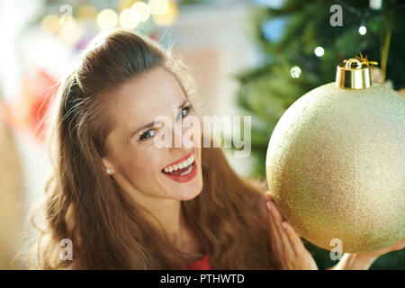 Portrait of smiling young woman with big gold Christmas ball near Christmas tree - Stock Image