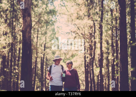 Couple of old caucasian senior travelers with backpack enjoy the free adventure lifestyle walking together in the forest - free independente journey f - Stock Image