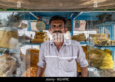 A portrait of a Indian man in front of his food and snacks cart in a south Indian village - Stock Image