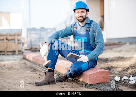 Portrait of a handsome builder in uniform mounting road borders on the construction site - Stock Image