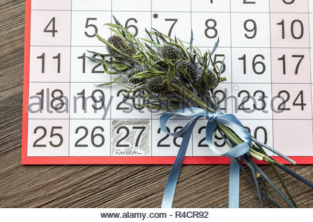 Funeral written on a calendar page and a posy of thistles - Stock Image