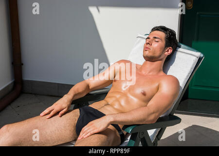 Young Man Sunbathing on Lounge Chair in Summer - Stock Image