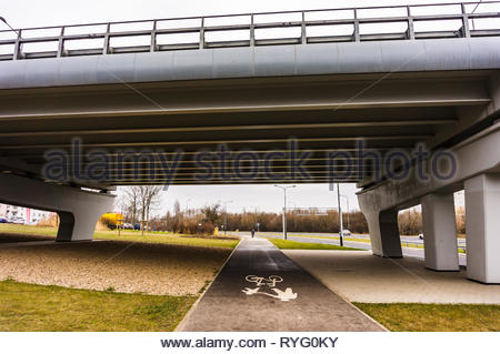 Poznan, Poland - March 3, 2019: Footpath and bike route under a bridge on the Inflancka street. - Stock Image