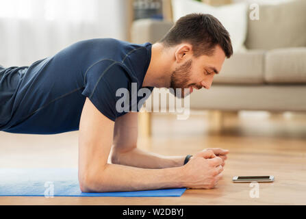 man doing plank exercise at home - Stock Image