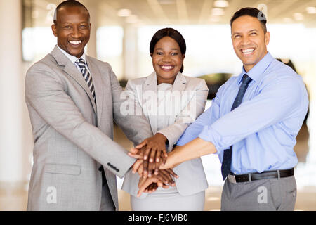 cheerful sales staff putting hands together in vehicle showroom - Stock Image