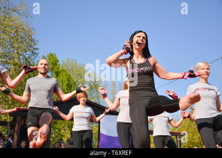 Nis, Serbia - April 20, 2019 Piloxing sport training group of people on sunny spring day outdoor with happy instructor - Stock Image