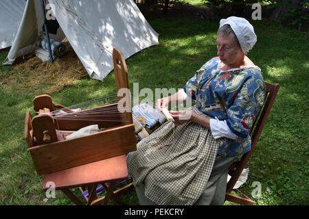 A woman giving a demonstration of using a Hand Loom from colonial times. - Stock Image
