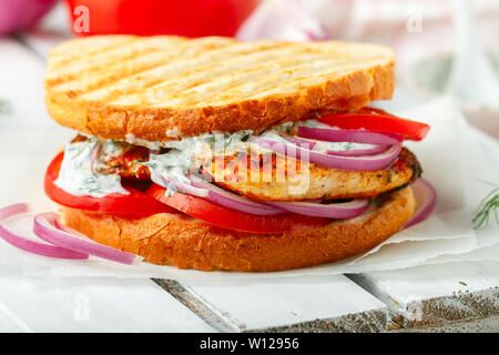 Sandwich with fried chicken breast, tomatoes, red onions and tzatziki sauce. Gourmet appetizer. Selective focus - Stock Image