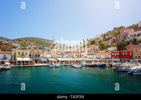 Hydra, Greece - June 2, 2018: Beautiful harbor with cycladic architecture hillside town behind, on the Greek Island of Hydra. Central Clock tower in H - Stock Image