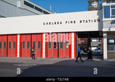 A man and two women walking past Chelsea fire station in King's Road, London, England, UK - Stock Image