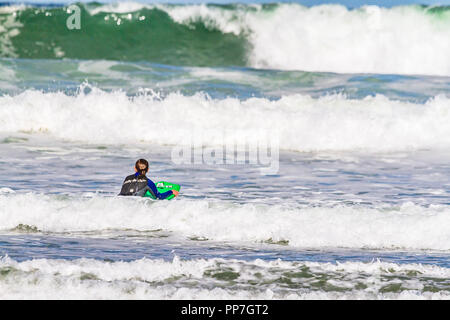 Northumberland, UK. 24th September, 2018. UK Weather: Bodyboarders take to the sea on a  warm, partly sunny afternoon at Bamburgh, Northumberland, UK. Credit: © NBSN / Alamy Live News - Stock Image