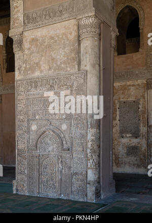 Engraved stone wall with floral patterns and calligraphy in front of the foundation stone of Ahmed Ibn Tulun Mosque with engraved formation text - Stock Image