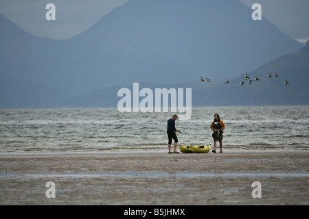 People sea kayaking in Applecross Wester Ross Scotland while oyster catchers fly past Picture by Ashley Coombes - Stock Image