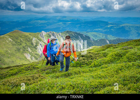 Two kids with their mom are hiking in highlands of Ciucas mountains, Romania - Stock Image