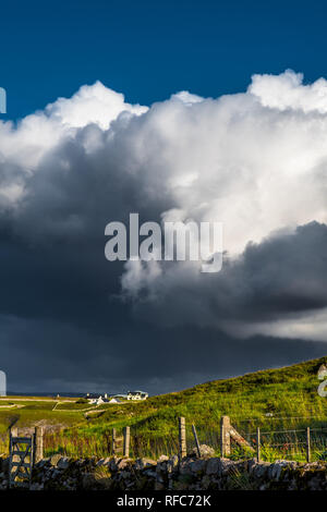 Remote Farm House In Front Of Heavy Clouds In The Highlands Of Scotland - Stock Image