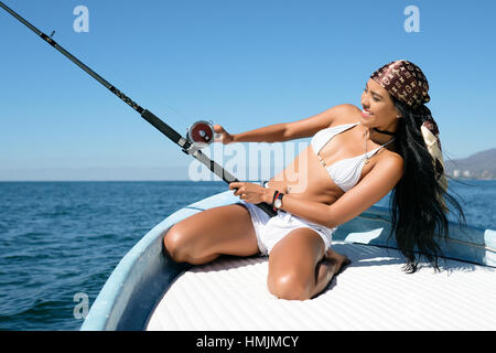 Attractive young hispanic woman leaning back while trying to reel in her catch at fishing off a boat. She looks - Stock Image