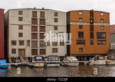 Old wooden buildings alongside a harbour channel in the town of Trondheim in Norway. - Stock Image