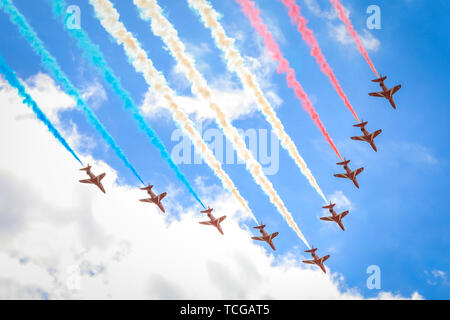 Trafalgar Square, London, UK, 08th June 2019. The Red Arrows for the Queen's Birthday Parade, Trooping the Colour,  flyover against the blue sunny sky, seen from Trafalgar Square. - Stock Image