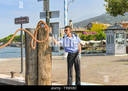 TORRI DEL BENACO, LAKE GARDA, ITALY - SEPTEMBER 2018: Crew member on the harbour side, catching a rope from a ferry docking at Torri del Benaco - Stock Image