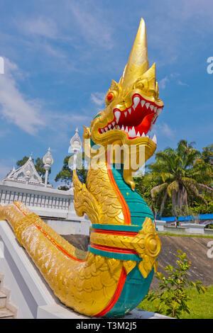 Golden naga sculpture, stairway leading up to Wat Kaew, Krabi town, Thailand - Stock Image