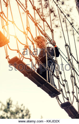 boy walking on rope bridge - Stock Image