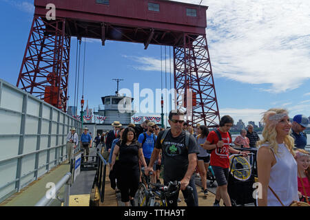 Visitors to Governors Island in New York harbor disembark from the new ferry on its first day of service, connecting Governors Island with the Battery - Stock Image