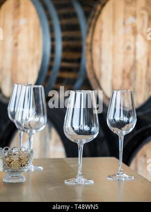 Empty wine glasses in front of wooden wine barrels. - Stock Image