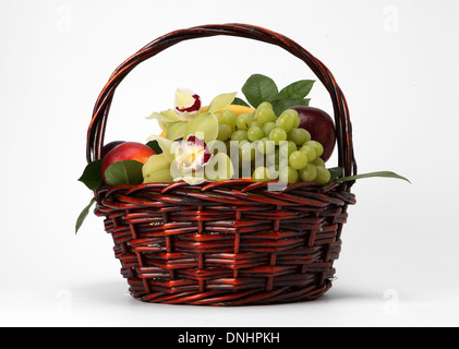 A basket filled with assorted fruit on a white background - Stock Image