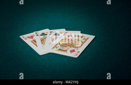 poker game of kings unfolded cards on green carpet - Stock Image