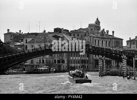 Motorboat approaching a ridge of tourists in Venice, Italy, monochrome - Stock Image