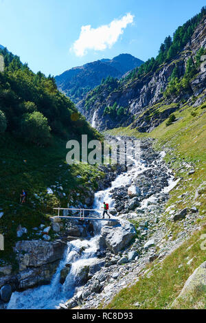 Hiker crossing narrow bridge, Mont Cervin, Matterhorn, Valais, Switzerland - Stock Image