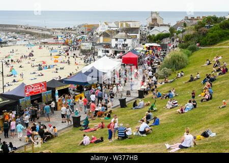 Lyme Regis, Dorset, UK.  13th July 2019. UK Weather.  Visitors flock to a food festival above the beach as they enjoying themselves at the seaside resort of Lyme Regis in Dorset on a warm cloudy day.  Picture Credit: Graham Hunt/Alamy Live News - Stock Image