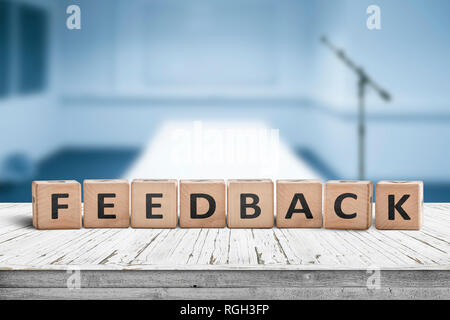 Feedback word on wooden cubics in a blue room on an old desk - Stock Image