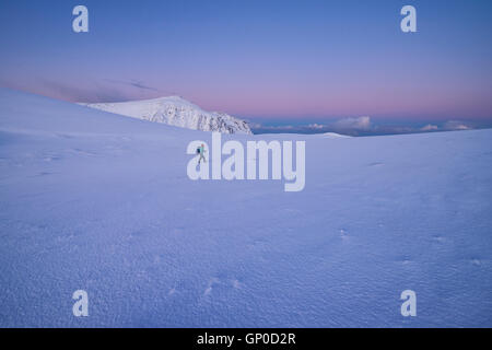 Female hiker walking across empty winter mountain landscape at dawn, Moskenesøy, Lofoten Islands, Norway - Stock Image